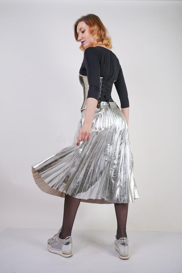 Pi?kna caucasian dziewczyna jest ubranym futurystycznego pvc gorsecika i szkockiej kraty kruszcow? sp?dnic? z odzwierciedlaj?cymi obrazy royalty free