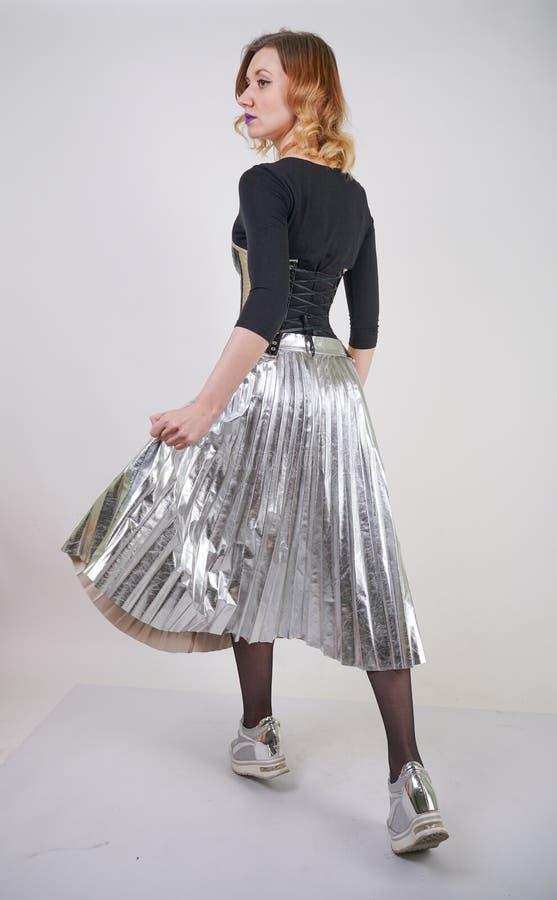 Pi?kna caucasian dziewczyna jest ubranym futurystycznego pvc gorsecika i szkockiej kraty kruszcow? sp?dnic? z odzwierciedlaj?cymi zdjęcia stock