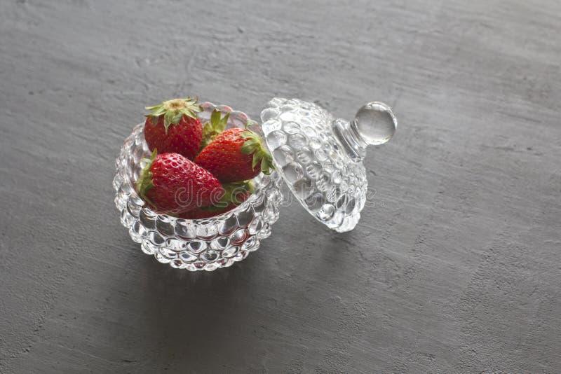 Pi?kna czerwona truskawka w szklanym round pucharze Truskawki na czarnym zmroku betonu tle Wie?niaka styl horyzontalny zdjęcia royalty free