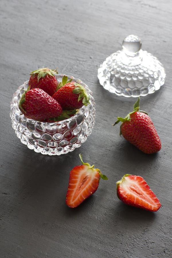 Pi?kna czerwona truskawka w szklanym round pucharze Truskawki na czarnym zmroku betonu tle Wie?niaka styl horyzontalny zdjęcie royalty free