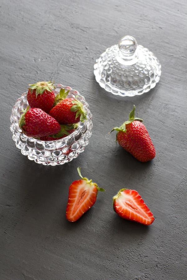 Pi?kna czerwona truskawka w szklanym round pucharze Truskawki na czarnym zmroku betonu tle Wie?niaka styl pionowo minimalista obrazy stock