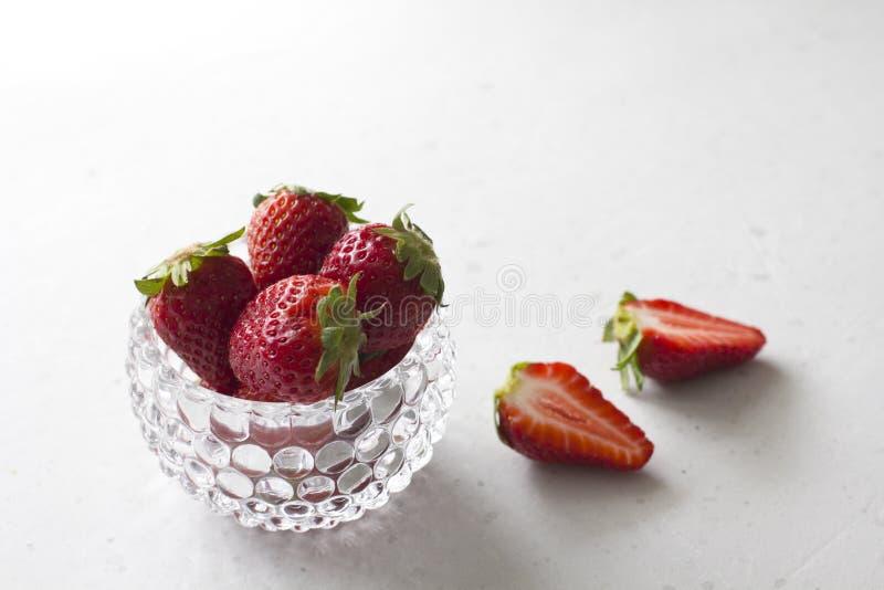 Pi?kna czerwona truskawka w szklanym round pucharze Truskawki na lekkim bielu betonu tle Wie?niaka styl R?ni?te truskawki, fotografia stock