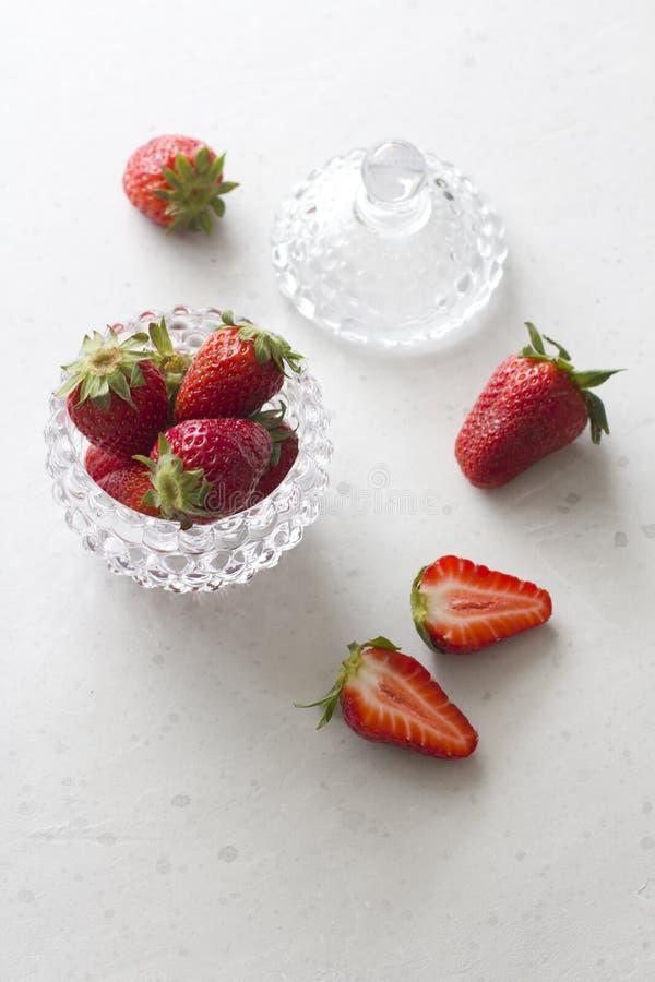 Pi?kna czerwona truskawka w szklanym round pucharze Zamkni?tym w g?r? Truskawki na lekkim bielu betonu tle Wie?niaka styl ci?cie obrazy royalty free