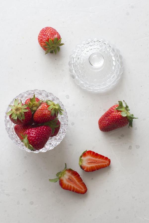 Pi?kna czerwona truskawka w szklanym round pucharze Zamkni?tym w g?r? Truskawki na lekkim bielu betonu tle Wie?niaka styl ci?cie fotografia stock