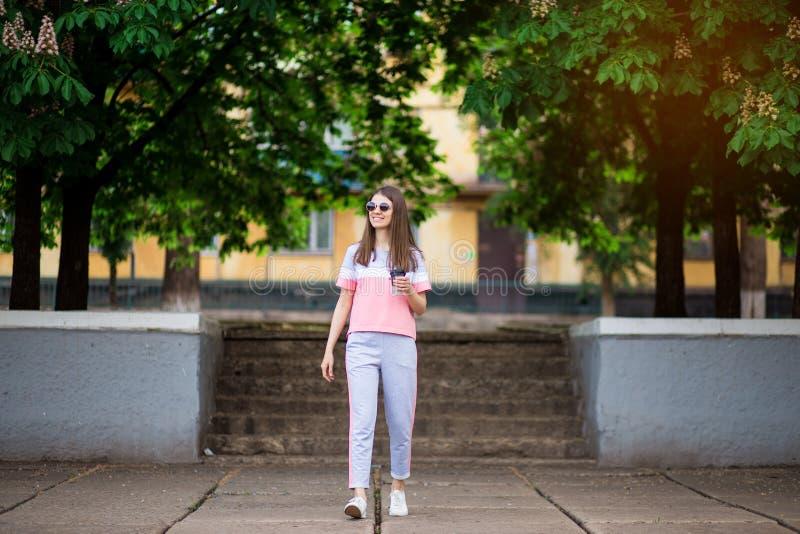 Pi?kna dziewczyna w okularach przeciws?onecznych chodzi lato ulic? z kaw? zdjęcie royalty free