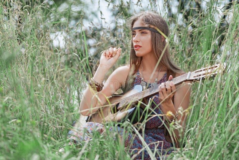 Pi?kna hipis dziewczyna z gitary obsiadaniem na lasowej hali?nie zdjęcia royalty free