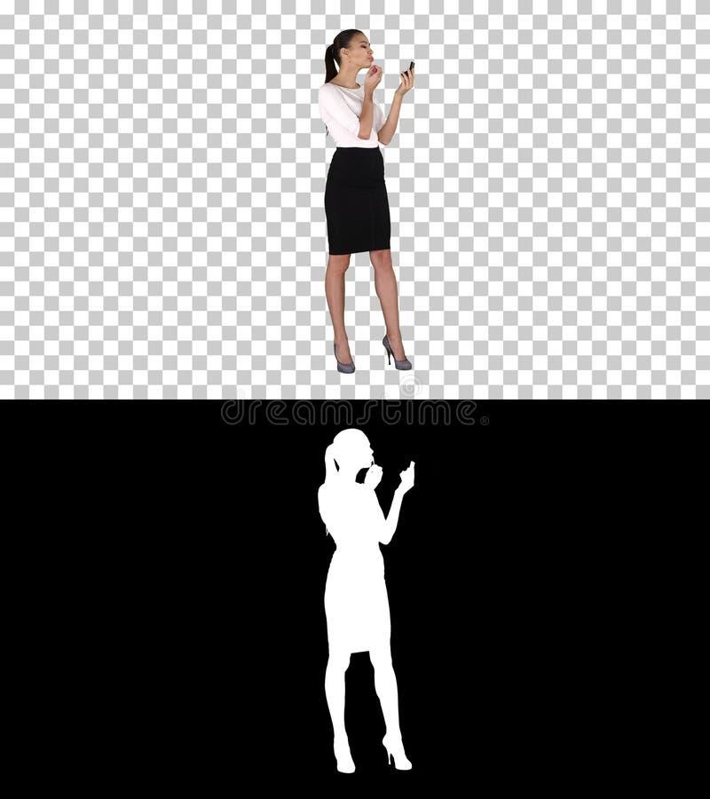 Pi?kna kobieta, barwid?a jej wargi pomadki menchie, patrzeje w lustrze, alfa kana? fotografia stock