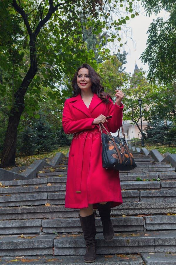 Pi?kna kobieta w czerwonym ?akieta odprowadzenia puszku schodki zdjęcia royalty free