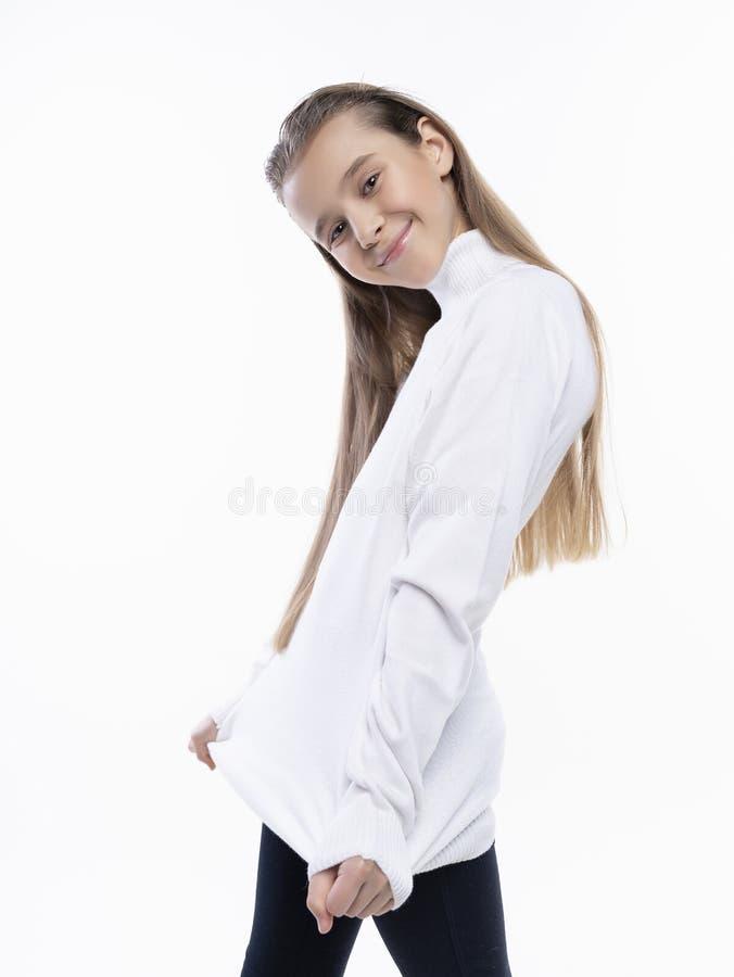 Pi?kna ?liczna nastoletnia dziewczyna jest ubranym bia?ego turtleneck pulower, cajgi u?miecha si? pozowa? i Na bia?ym tle reklamo zdjęcie royalty free