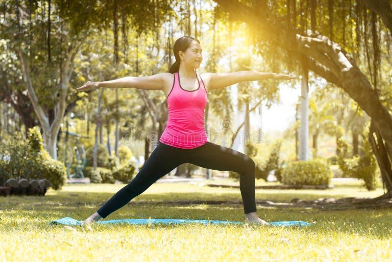 Pi?kna m?oda Azjatycka kobieta jest treningu ?wiczenia joga w parku fotografia stock