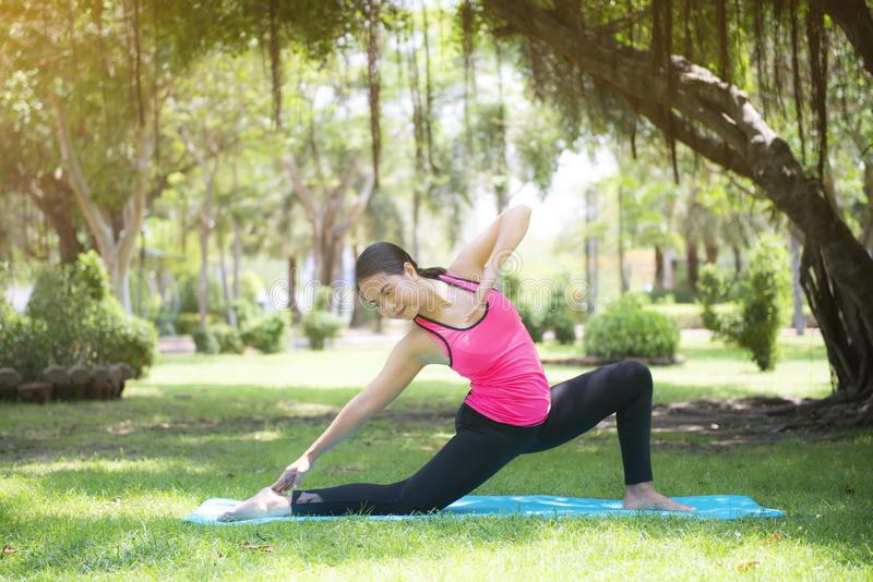 Pi?kna m?oda Azjatycka kobieta jest treningu ?wiczenia joga w parku zdjęcie stock