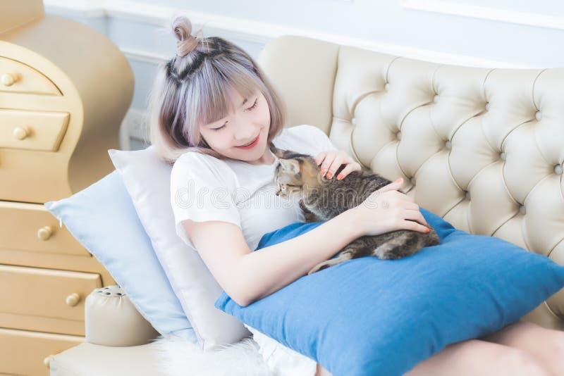 Pi?kna m?oda Azjatycka Tajlandzka kobieta k?ama? na kanapie z jego kotem szcz??liwie i muska? kot g?ow? z mi?o?ci? obrazy stock