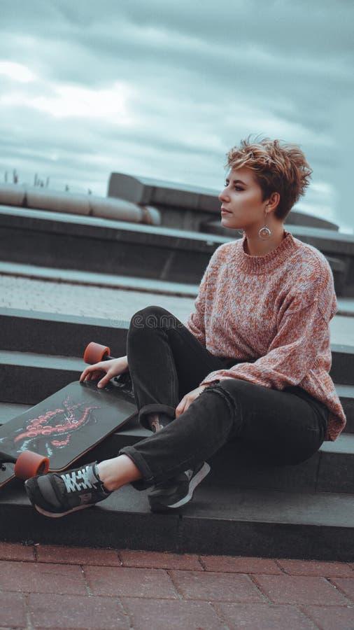 Pi?kna m?oda dziewczyna trzyma deskorolka podczas gdy siedz?cy w skatepark obraz stock