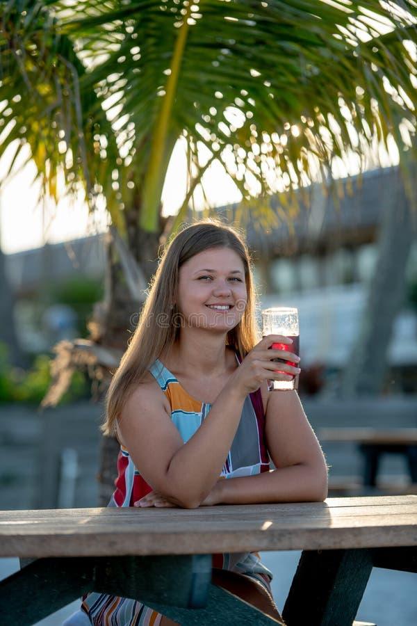 Pi?kna m?oda kobieta pije sok na pla?y zdjęcie royalty free