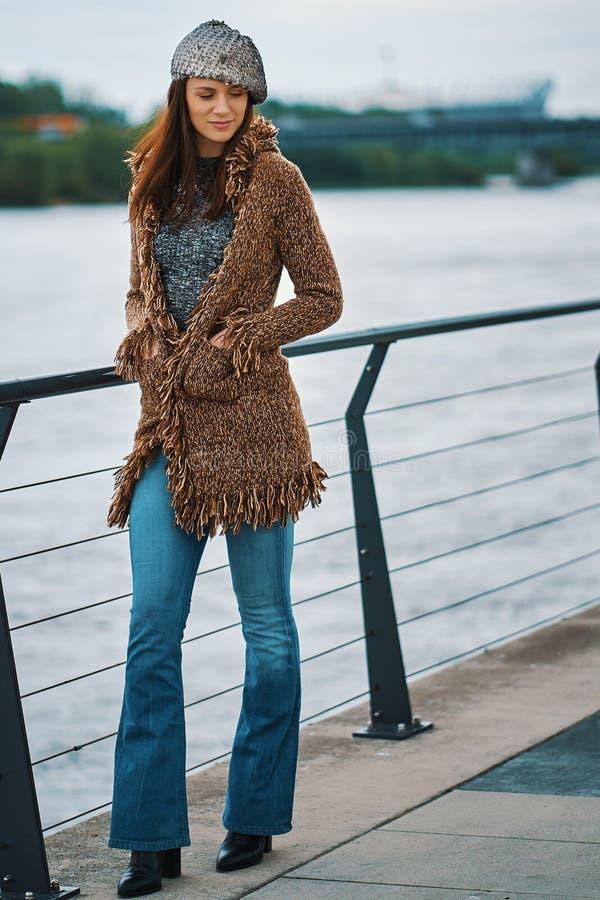 Pi?kna m?oda kobieta pozuje na deptaku przy rzek? w mie?cie zdjęcia stock