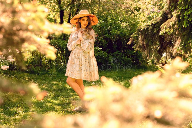 Pi?kna m?oda kobieta pozuje w parku Lato kapelusz i suknia zdjęcia royalty free
