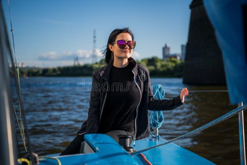 Pi?kna m?oda kobieta siedzi na jacht pozach i pucharze Jest ubranym sunglusses z ręką i uśmiechem Model żegluje na pokładzie obraz royalty free