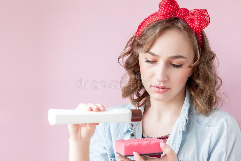 Pi?kna m?oda kobieta w g?r? z makija?em i fryzura z czy?ci narz?dziami na r??owym tle zdjęcia stock