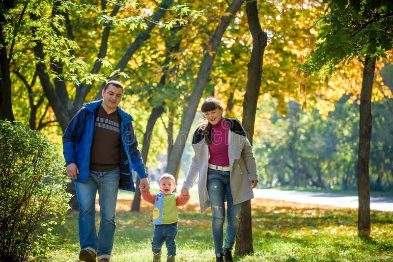Pi?kna m?oda rodzina na spacerze w jesie? lesie na klonowym ? obraz royalty free