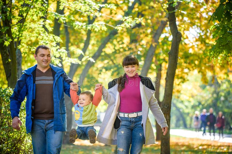 Pi?kna m?oda rodzina na spacerze w jesie? lesie na klonowym ? zdjęcia stock