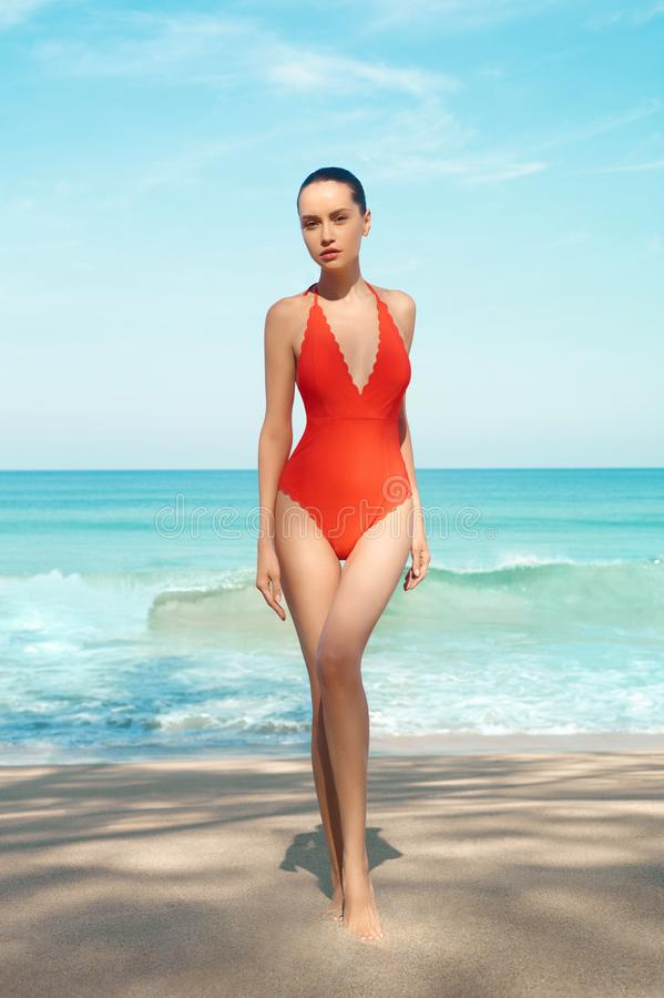 Pi?kna seksowna kobieta w czerwonym swimwear na pla?y obraz royalty free