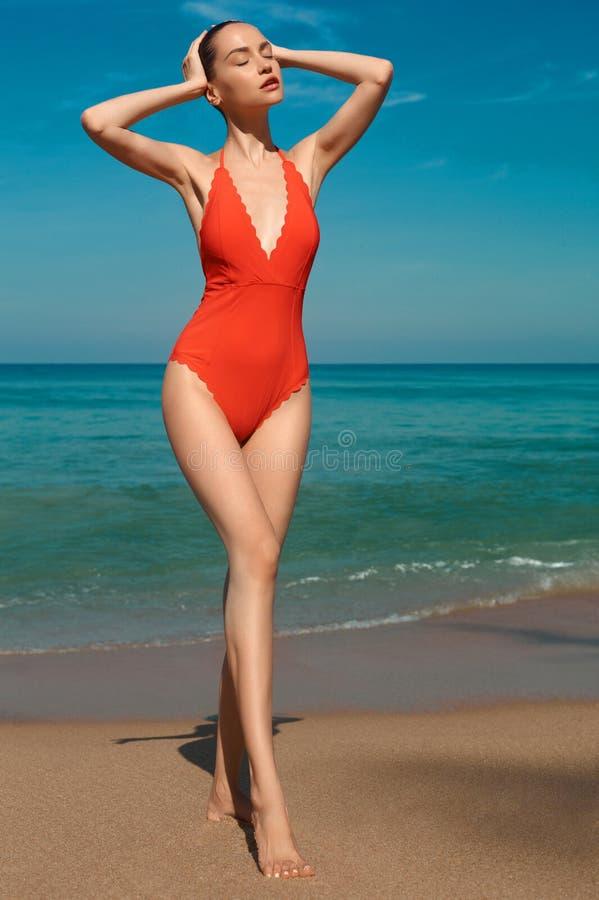 Pi?kna seksowna kobieta w czerwonym swimwear na pla?y zdjęcia stock