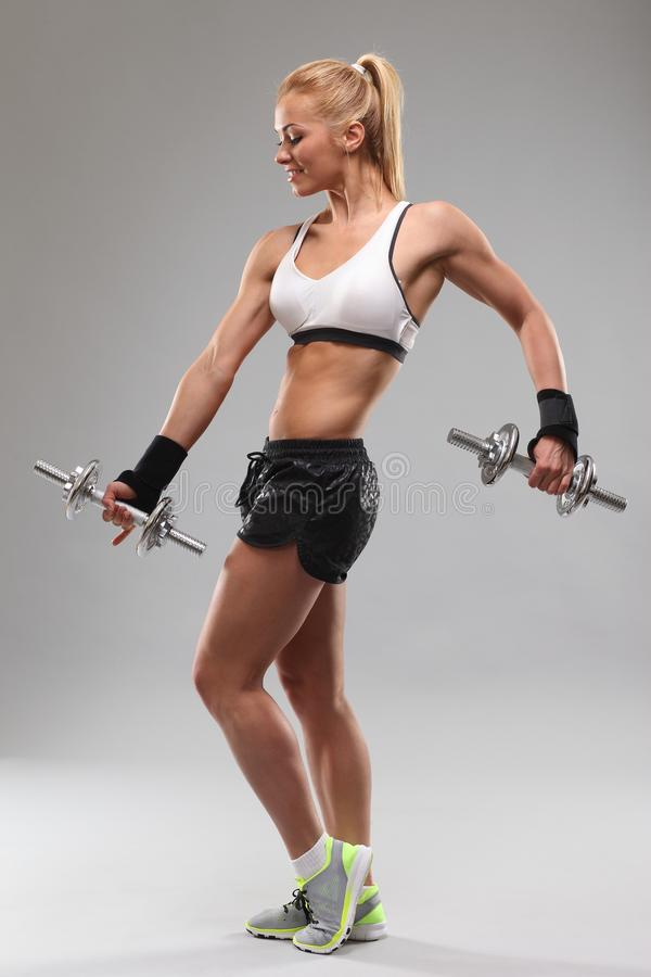 Pi?kna sporty kobieta pracuj?ca z dumbbells out zdjęcie royalty free