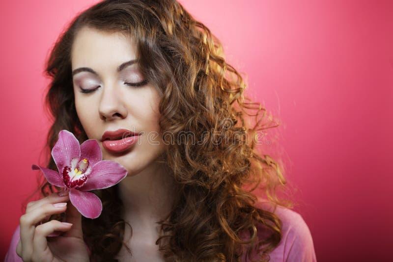 Pi?kna szcz??liwa kobieta z storczykowym kwiatem nad r??owym t?em fotografia royalty free