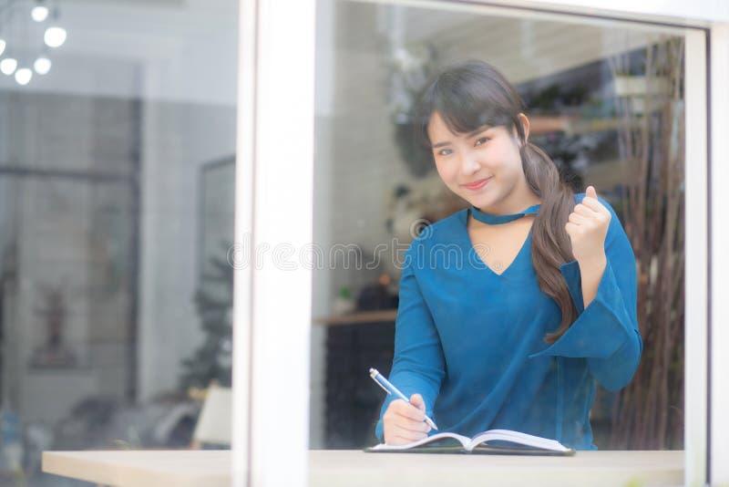 Pi?knego portreta kobiety m?ody azjatykci pisarz pisze na notatniku lub dzienniczku z szcz??liwym i z podnieceniem zdjęcia royalty free