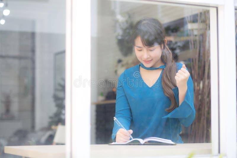 Pi?knego portreta kobiety m?ody azjatykci pisarz pisze na notatniku lub dzienniczku z szcz??liwym i z podnieceniem zdjęcie royalty free