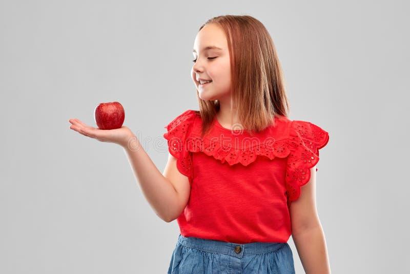 Pi?knego u?miechni?tego dziewczyny mienia czerwony jab?ko na palmie zdjęcia stock
