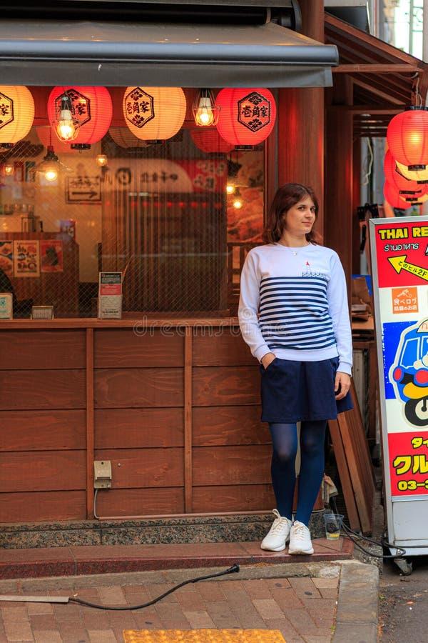 Pi?kni dziewczyna stojaki blisko Japo?skiej restauracji w Tokio obrazy stock