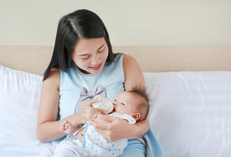 Pi?kny azjata matki karmienia mleko jej niemowlak butelk? na ? zdjęcia stock