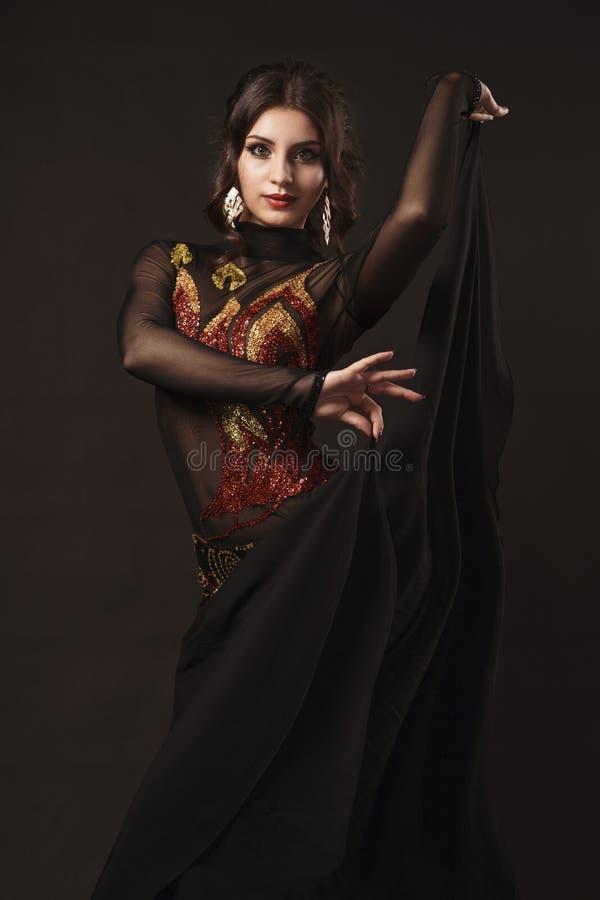 Pi?kny brzucha tancerz perfoming egzotycznego tana w czerwonej flatter sukni zdjęcie stock