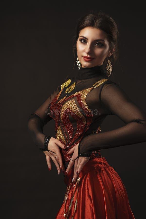 Pi?kny brzucha tancerz perfoming egzotycznego tana w czerwonej flatter sukni obraz stock