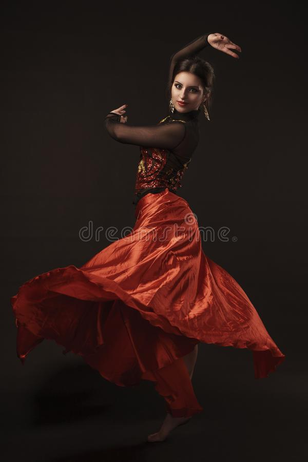 Pi?kny brzucha tancerz perfoming egzotycznego tana w czerwonej flatter sukni fotografia royalty free