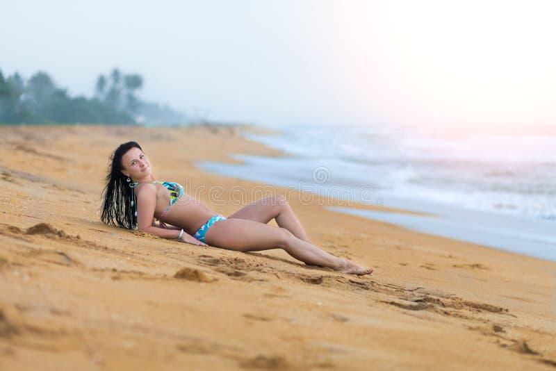 Pi?kny kobiety lying on the beach na piasku na pla?y w lecie Wakacje szcz??cia beztroska radosna kobieta zdjęcie royalty free