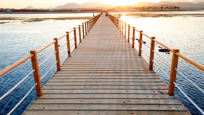 Pi?kny krajobraz spokojne ocean fale i t?sk drewniany molo Zadziwiaj?cy jetty przy dennym aagainst zmierzchem nad g?rami zdjęcie royalty free