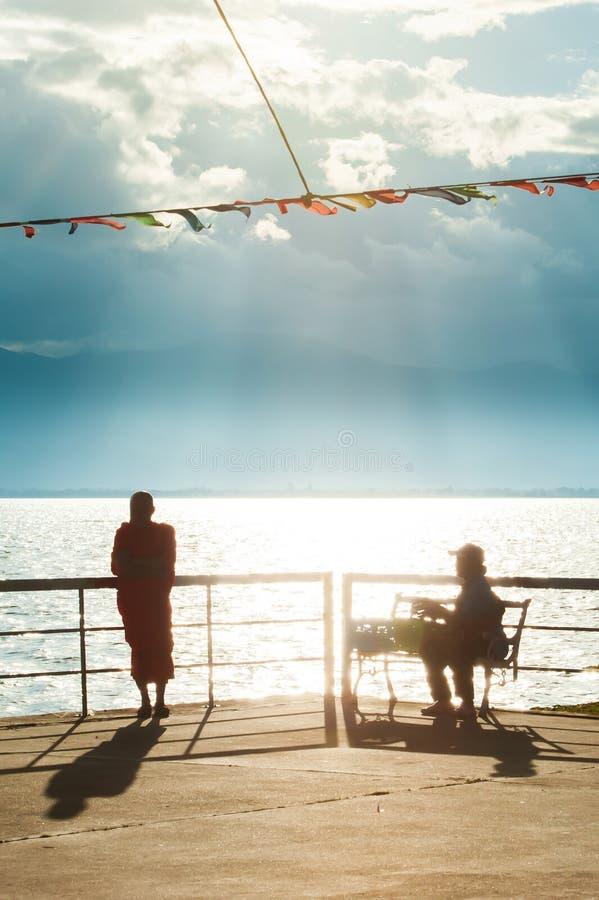 Pi?kny lato, pokojowy sceniczny brzeg jeziora przy p??mrokiem, mnisi buddyjscy i ludzie relaksuje w zmierzchu ?wietle, sunbeam pr zdjęcie stock