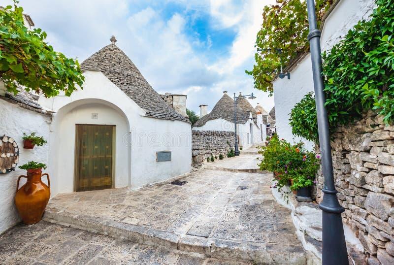 Pi?kny miasteczko Alberobello z Trulli domami w?r?d zielonych ro?liien i kwiat?w, Apulia region, Po?udniowy W?ochy zdjęcia stock