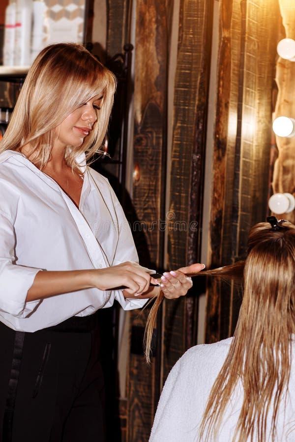 Pi?kny u?miechni?ty blond hairstylist z jej klientem w fryzjerze Opieka, zaw?d, kosmetologia, zdr?j, pi?kno salon fotografia stock