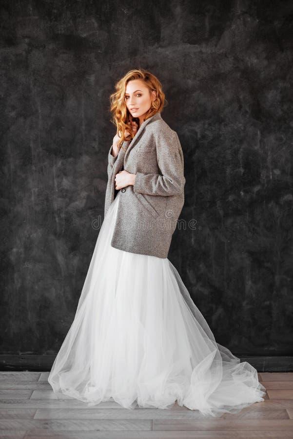 Pi?kny u?miechni?ty blondynki kobiety model w eleganckim ciemnym p?aszczu i biel ubieramy fotografia stock