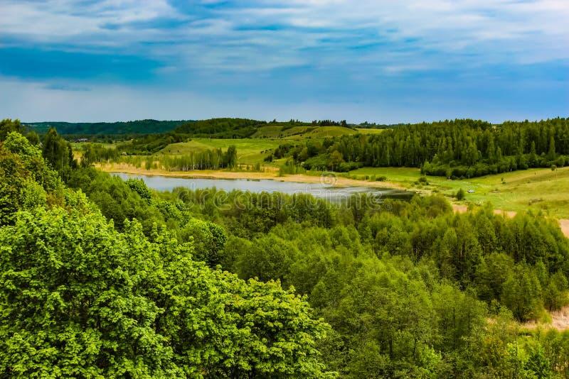 Pi?kny wiejski lato krajobraz z lasem, rzek?, niebieskim niebem i bielem, chmurnieje obrazy royalty free