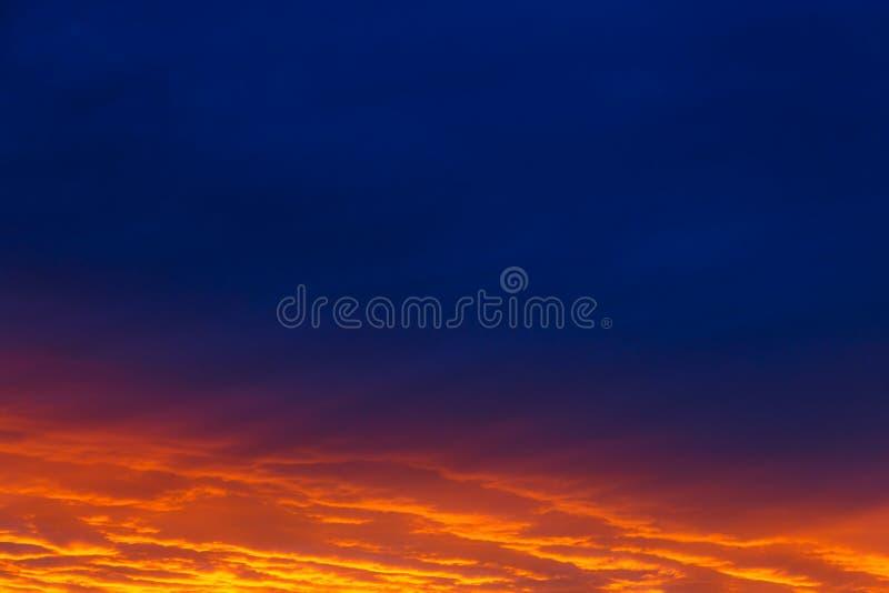 pi?kny zach?d s?o?ca Kolorowy dramatyczny niebo przy zmierzchem Płatowate podeszczowe chmury Jaskrawy błękitny pomarańczowy tło zdjęcia royalty free