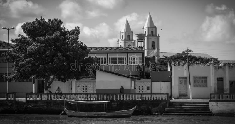 Piacabucu/Alagoas/Brazil - Apr.13.19: men seated under the shadow of a tree, houses, church and a boat on the river. Black and white royalty free stock images