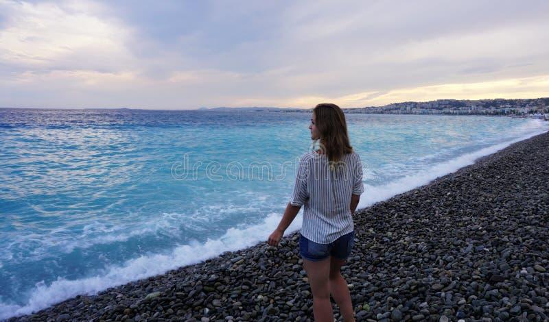 Piacevole, Francia Giovane donna che gode della costa azzurrata e che esamina il mare immagine stock