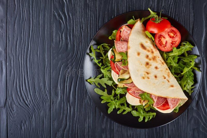 Piadina italiano con la mozzarella, tomate, salami imagen de archivo libre de regalías