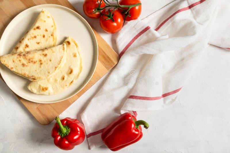 Piadina italiano recentemente cozido em uma placa branca com tomates e pimenta dos vegetais no fundo branco Vista superior, espa? imagens de stock