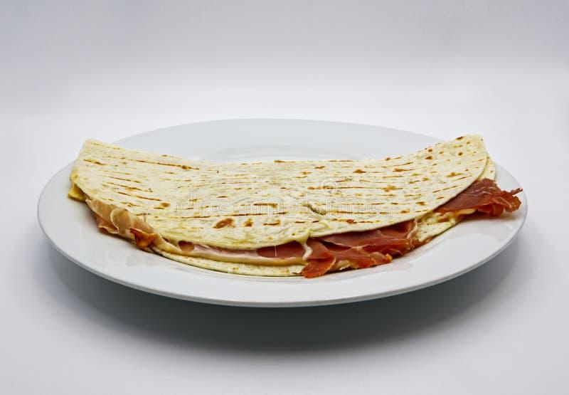 Piadina romagnola 意大利小面包干用火腿和乳酪,在白色背景 免版税库存照片
