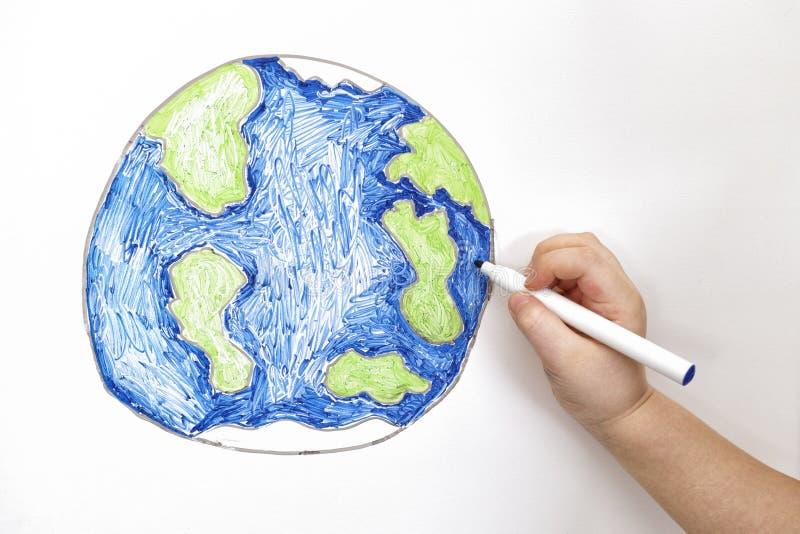 Pianeta Terra del disegno della mano del ` s del bambino con un indicatore immagini stock